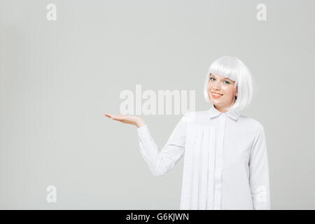 Cheerful beautiful young woman in blonde wig holding copyspace on palm over white background