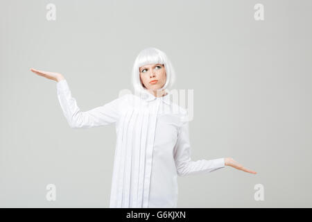 Thoughtful confused young woman in blonde wig holding copyspace on two palms over white background