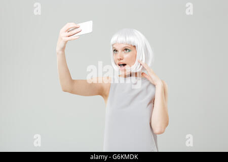 Smiling playful young woman making selfie using smartphone over white background - Stock Photo