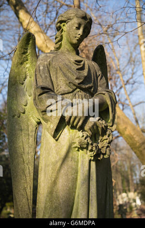 close-up of stone sculpture of angel on sunny winter's day in Highgate cemetery, north London - Stock Photo