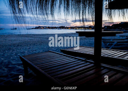 Mallorca, Straw umbrellas and beach chairs on the beach at sunset - Stock Photo