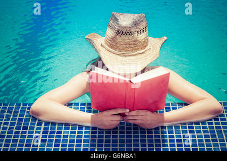 Woman wearing straw hat reading book at pool edge - Stock Photo