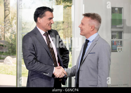 Confident and successful business men shaking hands in a large cooperate modern office - Stock Photo