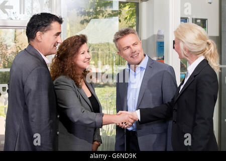 Successful and happy business people standing and shaking hands at office entrance after inspiring business meeting - Stock Photo