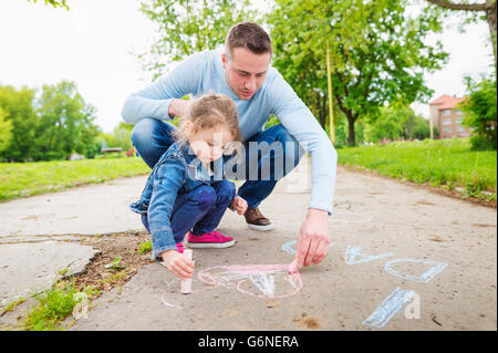 Father and daughter drawing with sidewalk chalk - Stock Photo