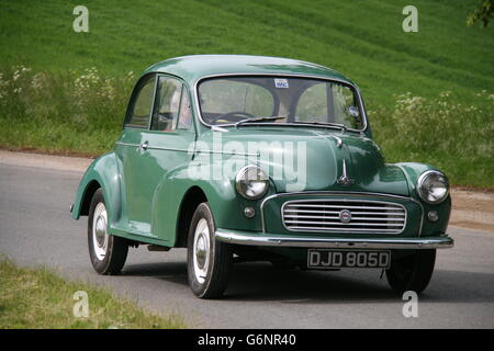 A GREEN MORRIS MINOR 1000 SALOON CAR TRAVELLING ROUND A BEND ON A NARROW COUNTRY LANE - Stock Photo