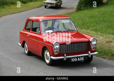 A FRONT OFFSIDE VIEW OF A RED AUSTIN A40 FARINA CLASIC CAR GOING ROUND A BEND ON A NARROW COUNTRY LANE EN ROUTE - Stock Photo