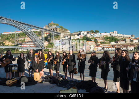 Young students from Abel Salazar Biomedical Sciences Institute, performing to tourists in the city of Porto, Portugal - Stock Photo