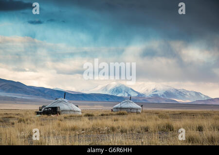 two yurts in a landscape of western Mongolia with snowy mountains at the backgrounds - Stock Photo