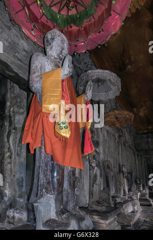 Buddha in saffron shawl on an interior corridor of Angkor Wat, Cambodia - Stock Photo