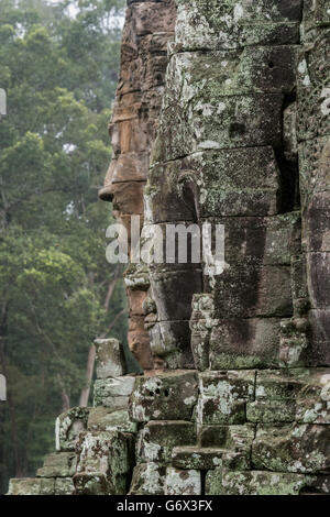 Compassionate buddha faces (Lokesvaras) in the rain, Prasat Bayon, Angkor Thom, Cambodia - Stock Photo