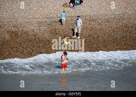 People enjoying the sunny weather on Brighton beach in Sussex. Stock Photo