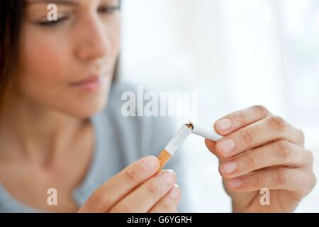 MODEL RELEASED. Young woman breaking a cigarette in half. - Stock Photo