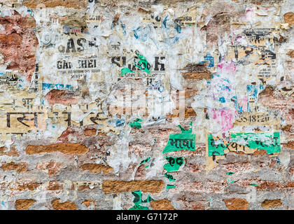 Grungy brick wall texture with torn posters in Kathmandu, Nepal - Stock Photo
