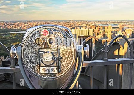 Shiny metal public viewing binoculars set against a blue ...