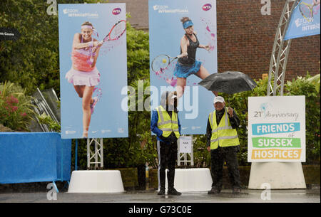 The stewards carry on smiling despite the torrential rain during The Aegon International Tournament at Devonshire - Stock Photo