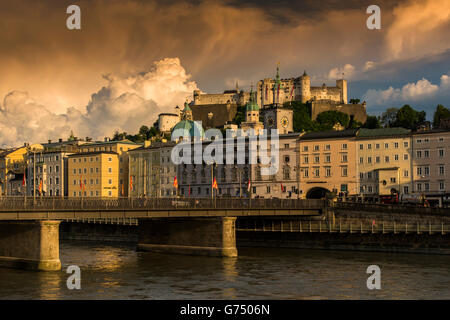 Sunset view of Hohensalzburg castle with erupting thunder cloud behind, Salzburg, Austria - Stock Photo