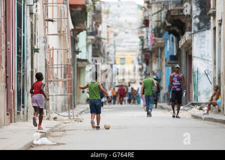Young boys playing football in a street in Havana, Cuba - Stock Photo