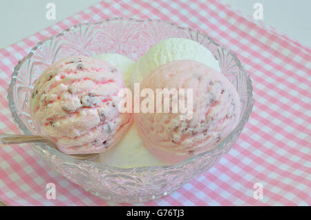 scoops of strawberry ice cream and vanilla ice cream in a bowl on a white and pink checkered napkin, macro, close - Stock Photo