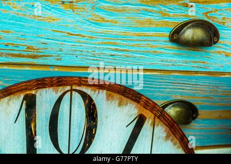 Part of an old clock dial in front of old blue shabby chic  furniture drawers - Stock Photo