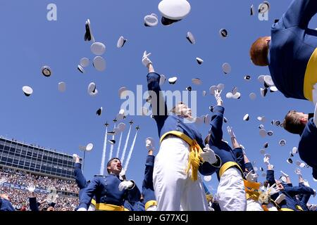 U.S Air Force Academy cadets toss their caps into the sky as the Thunderbirds fly overhead during graduation ceremony - Stock Photo