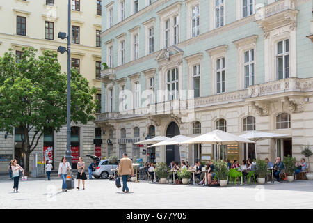 Street scene of Freyung with outdoor cafe terrace and people in old city centre of Vienna, Austria - Stock Photo