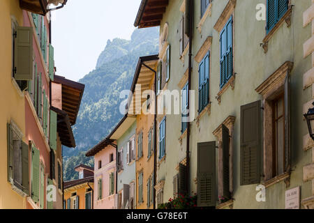 View of old picturesque narrow street in the town of Riva del Garda, with mountain top beyond. - Stock Photo