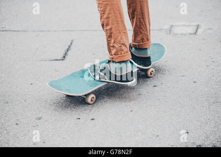 Young skateboarder in gumshoes standing on skate - Stock Photo