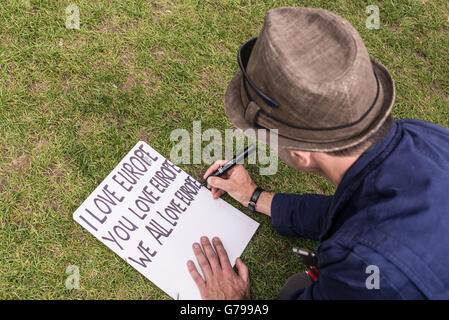 Westminster, London, UK. 25th June, 2016. Man writing 'I love Europe' on a poster as part of protests against Brexit - Stock Photo