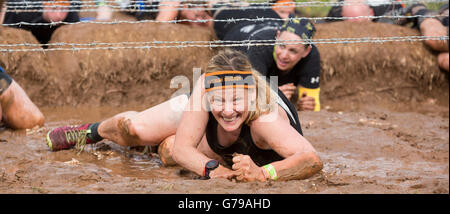 Tough Mudder, a muddy wet girl takes on the Kiss of Mud obstacle at Drumlanrig Castle, Dumfries and Galloway, Scotland, - Stock Photo