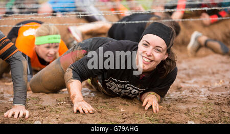 Tough Mudder obstacle course, girl smiling in mud on the Kiss of Mud obstacle Drumlanrig Castle, Dumfries and Galloway, - Stock Photo
