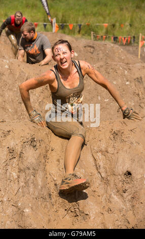 Muddy girl on Mud Mile obstacle on the Tough Mudder obstacle course at Drumlanrig Castle, Dumfries and Galloway, - Stock Photo