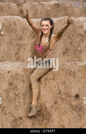 One happy pretty smiling girl covered in mud taking part in the Tough Mudder on the Mud Mile at Drumlanrig Castle, - Stock Photo