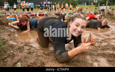 Happy girl crawling through mud on the Kiss of Mud obstacle gives it the thumbs up. Tough Mudder at Drumlanrig Castle, - Stock Photo
