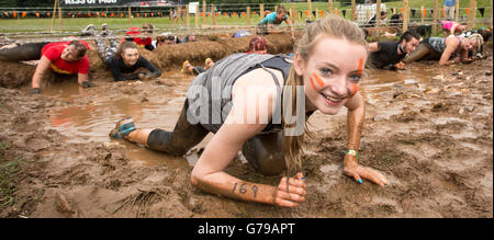 Girl crawling under barbed wire on the Kiss of Mud obstacle on Tough Mudder at Drumlanrig Castle, Dumfries and Galloway, - Stock Photo
