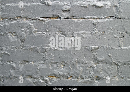 Detail of a brick wall close-up, smeared with cement and painted over with a thick layer of gray paint for use as a background.