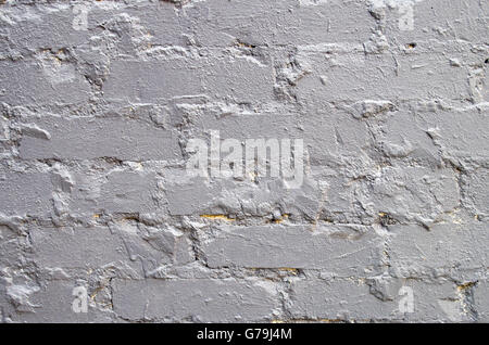 Fragment of a brick wall closeup, smeared with cement and painted over with a thick layer of gray paint for use as a background.