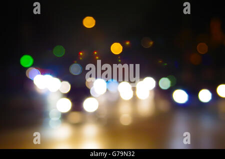 Abstract blurred night scene on city road. Defocused lights from the headlights of cars and the night lights of - Stock Photo
