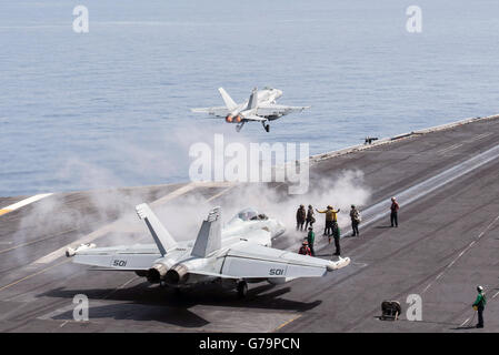A US Navy F/A-18C Hornet fighter aircraft launches from the flight deck of the aircraft carrier USS Harry S. Truman - Stock Photo