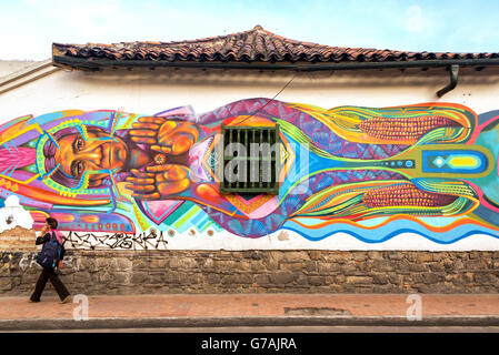 Woman walking past graffiti with and indigenous theme in the historic center of Bogota, Colombia - Stock Photo