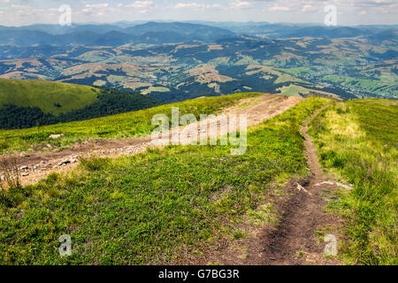 summer landscape. path goes ftom the mountain range down to village in valley at the mountain foot - Stock Photo