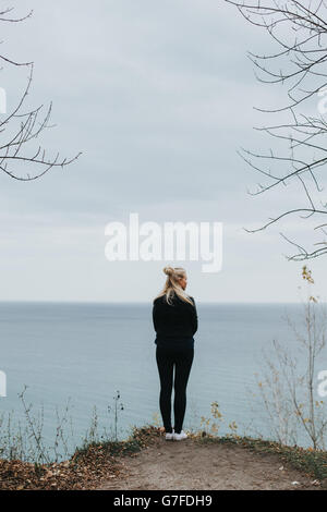 Girl standing on a cliff overlooking the lake - Stock Photo