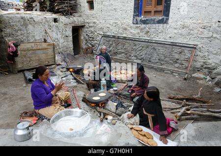Women preparing food for a festival, Samstanling Gompa, Sumur, Nubra Valley, near Leh, Ladakh, Jammu and Kashmir, - Stock Photo