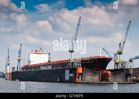 Container ship undergoing repairs in dry dock at  Port of Hamburg on River Elbe in Germany - Stock Photo