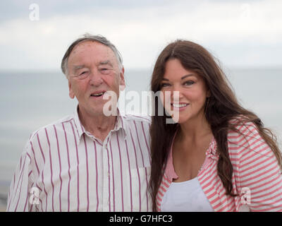 An old man and his niece enjoying a joke at the seaside. - Stock Photo