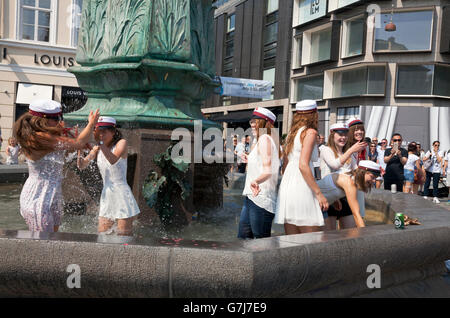 Happy Danish students celebrate their high school graduation with the traditional dip in the Stork Fountain on Stroeget - Stock Photo