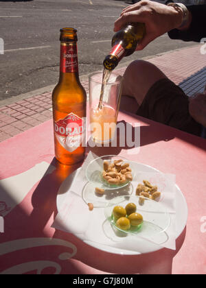 Sun shining through a brown Dorada bottle, mans hand pouring beer into half filled glass, nuts and olives, bar in - Stock Photo