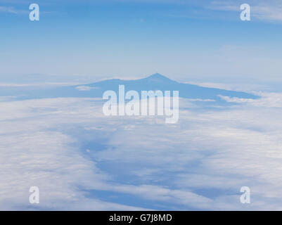 Tenerife with mount Teide in hazy blue and white seen from an approaching / leaving plane - Stock Photo