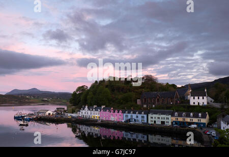 Colourful houses reflected in calm water Portree harbour at sunset. Isle of Skye, Scotland with distant hills in - Stock Photo