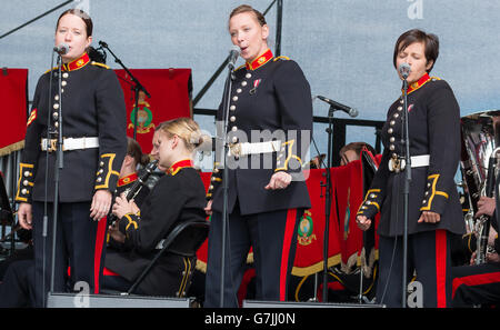 Three female soldiers from the British Army in dress uniform sing as part of a military band. Sunderland, United - Stock Photo